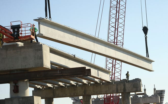 Construction workers set one of the concrete and steel support beams on the new overpass under construction on the University of Alabama campus , Dec. 8, 2020. [Staff Photo by Gary Cosby Jr.]
