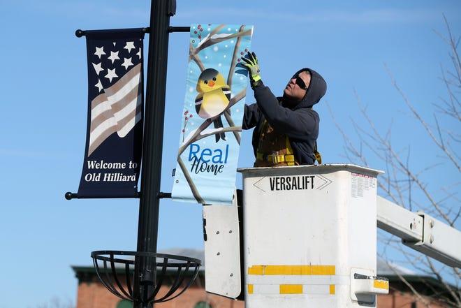 Matt Bailey, a Hilliard maintenance technician, hangs holiday banners on the street-light poles lining Main Street in Old Hilliard on Dec. 2.