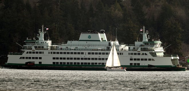 The Washington State Ferry Chimacum passes a sailboat as it heads into Rich Passage on Sunday, Dec. 7, 2020.