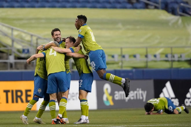 Seattle Sounders' Gustav Svensson (4) is surrounded by teammates after scoring the team's third, and winning, goal against Minnesota United in an MLS playoff Western Conference final soccer match, Monday, Dec. 7, 2020, in Seattle. The Sounders won 3-2.