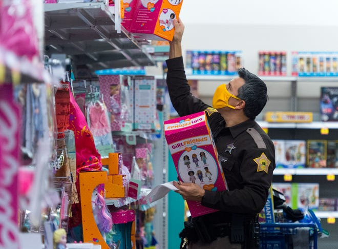 Vanderburgh County Sheriff Deputy Mike Brown reaches for a doll as he Christmas shops for kids with the Ark Crisis Child Care Center at Meijer in Evansville Tuesday morning, Dec. 8, 2020.