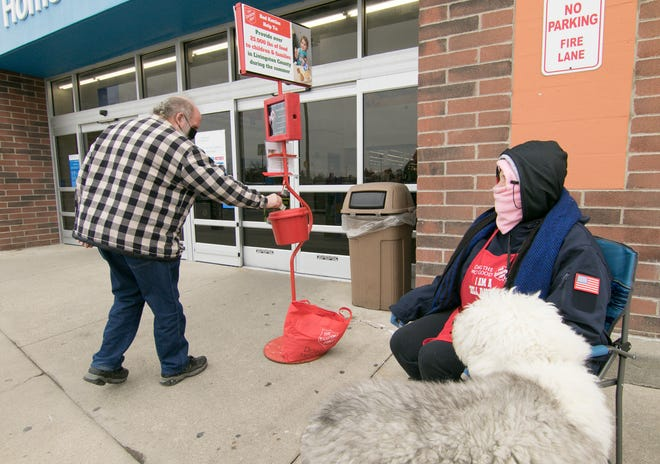 Whitmore Lake resident Bob Alexander places a donation in the Salvation Army red kettle in front of the Genoa Township Walmart, manned by Pollyann Walker and her sheepdog, Newton Tuesday, Dec. 8, 2020. Walker puts in eight-hour days five days a week wishing passers-by a merry Christmas and ringing the bell for the Salvation Army.