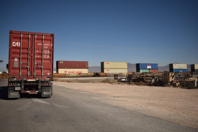 Truck waits for cargo train to pass in Santa Teresa, N.M. by the Union Pacific Intermodal Terminal.