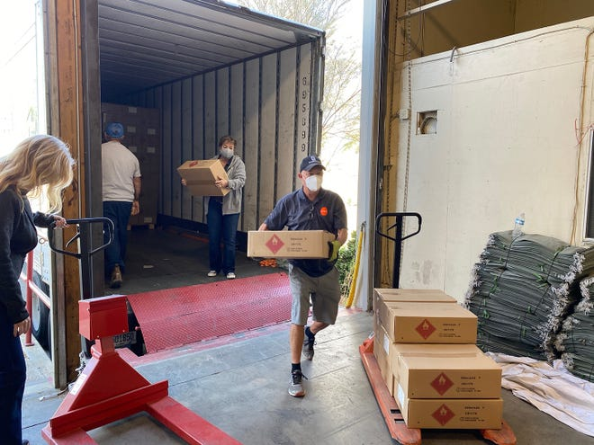 Staff from the Coachella Valley Economic Partnership unload a supply of personal protective equipment in preparation for distribution to Coachella Valley small businesses in December 2020.