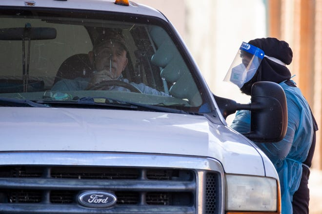 A person self-administers a nasal swab sample at a drive-through COVID-19 testing site on Indian School Road west of Goldwater Boulevard on Dec. 8, 2020, in Scottsdale, Ariz.