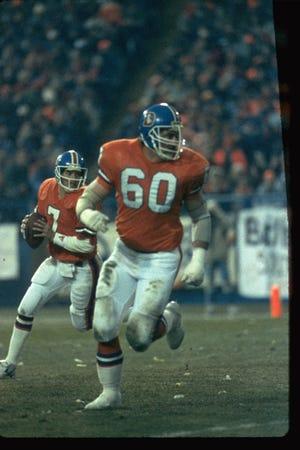 Former Denver Broncos offensive lineman Paul Howard (center) protects quarterback John Elway ((left).