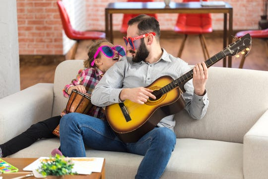 Little girl and her father with funny sunglasses sitting at home, playing a guitar and a drum.