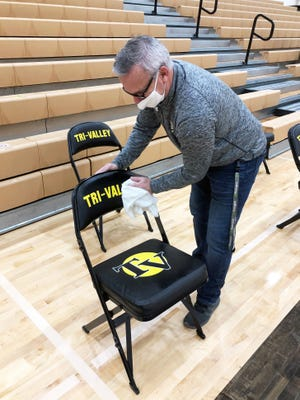Tri-Valley athletic director Erin Nezbeth santizes chairs following the girls basketball team's 61-47 win against Maysville on Dec. 5 in Dresden. Wiping down chairs, basketballs and other equipment is one of many preventative tasks that athletic personnel must juggle to prevent spread of COVID-19.