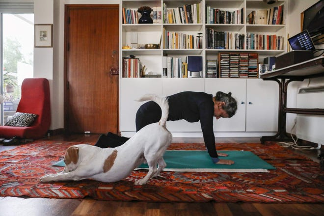 This picture taken on March 23, 2020 shows a woman taking part in an online pilates class at home, as her dog Elvis stretches next to her, in Nicosia, as restrictions on movement and social distancing were imposed across Cyprus to contain the spread of the COVID-19 novel coronavirus.