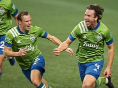 The Seattle Sounders' Gustav Svensson (4) celebrates with teammate Brad Smith (2) after scoring the winning goal against Minnesota United.