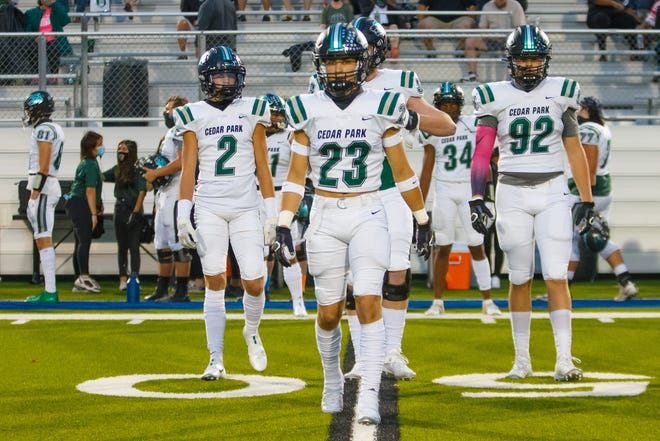 Cedar Park team captain Josh Bretz leads the Timberwolves onto the field against Hendrickson in a game earlier this season. Cedar Park began and ended the regular season ranked No. 1 in the Class 5A poll by the American-Statesman.