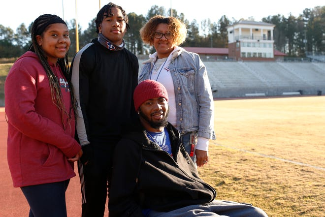 From left Teah, Dalen, Tish and Devon Gales pose for a photo at Jefferson Memorial Stadium. Devon suffered a paralyzing injury in a UGA football game and his brother, Dalen, after discussing with family, picked the game back up this season after years of not playing because of Devon's injury. Not pictured: Father, Donny. (Photo/Joshua L. Jones, Athens Banner-Herald)