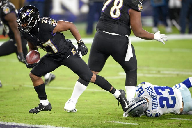 Baltimore Ravens running back J.K. Dobbins, left, gets by the tackle attempt of Dallas Cowboys strong safety Darian Thompson while scoring a touchdown during the second half Tuesday in Baltimore.