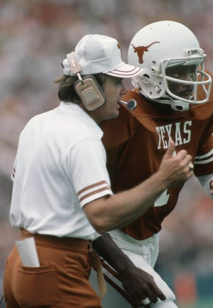 Texas Longhorns head coach Fred Akers talks to receiver Donnie Little on the field at Texas Memorial Stadium during the 1981 season. Akers passed away on Monday at the age of 82.