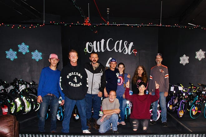 Members of Outcast 4 Christ Recovery Ministry and Sober Living gather beside the bikes purchased with money raised from their annual fundraiser. The group was able to purchase 43 bikes to be distributed to children in need.