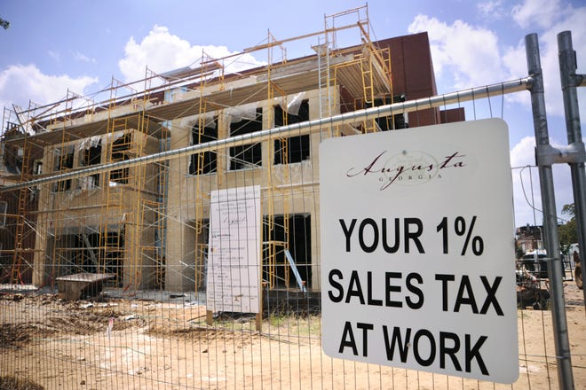 "A sign promoting ""Your 1% Sales Tax At Work"" hangs on a fence along Greene Street where the main Augusta library was under construction in 2009. The Augusta Commission recently approved a project list for SPLOST 8, which would go into effect next year if voters approve."