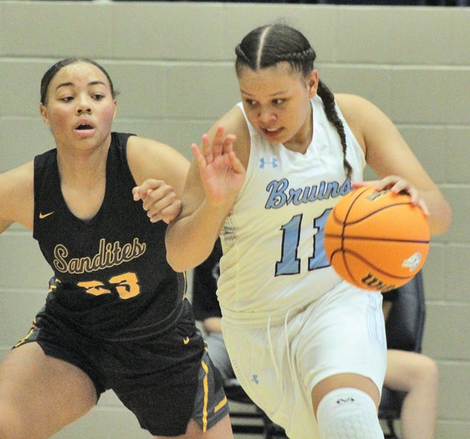 Bartlesville High's Mikka Chambers, right, displays total determination as she drives the ball during Tuesday's home-opener battle against Sand Springs.