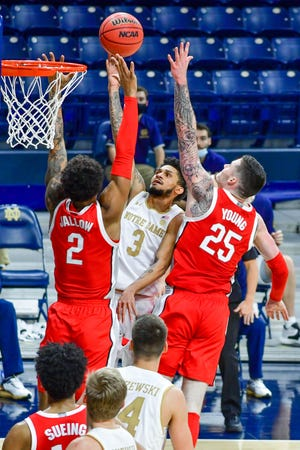 Dec 8, 2020; South Bend, Indiana, USA; Notre Dame Fighting Irish guard Prentiss Hubb (3) goes up for a shot as Ohio State Buckeyes guard Musa Jallow (2) and forward Kyle Young (25) defend in the second half at the Purcell Pavilion.