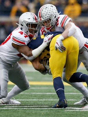 Ohio State linebackers Justin Hilliard, left, and Pete Werner combine to tackle Michigan running back Zach Charbonnet in last season's meeting in Ann Arbor. Michigan's cancellation of this year's game because of COVID-19 cases likely means the teams won't meet for the first time since the 1918 season.