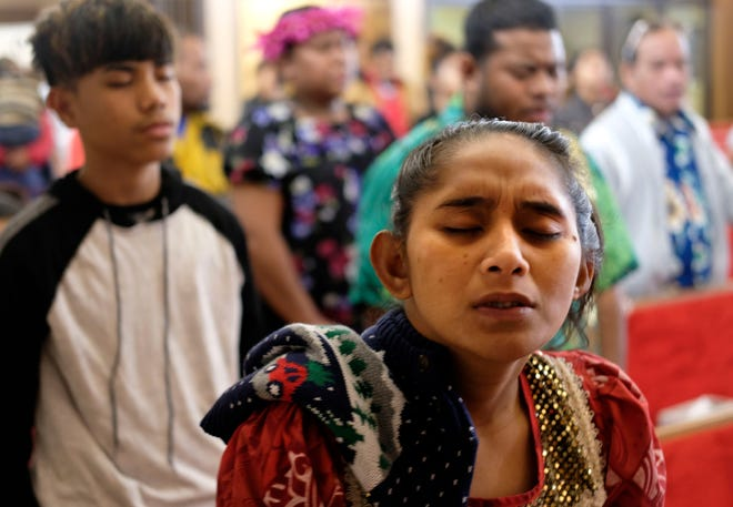 Joann Konou closes her eyes during an evening service at  Marshallese Throne in Jouj church  in Noel, Sunday, Nov. 22.