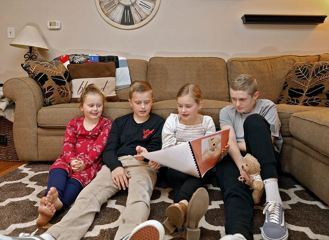 """Tess Short, 9, reads her book """"The Worry-Free Bear"""" to her siblings, from left, Mara, Colin and Sam at their house in Upper Arlington. Tess wrote the book about how a girl with cancer uses a teddy bear to bring comfort during challenging times after Sam began battling pediatric cancer."""