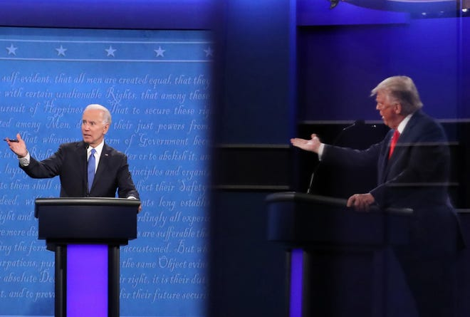 Democratic nominee Joe Biden and GOP President Donald Trump, shown in a reflection, participate in the final presidential debate at Belmont University on Oct. 22 in Nashville, Tennessee. Electoral College electors will cast ballots for the candidates Monday in Ohio and across the country.