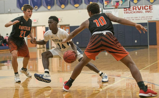 Eustis' Tyree Patterson (14) drives between Umatilla's Henry Clendinen (21) and Trey Craft (10) during Tuesday's game at the Panther Den in Eustis. [PAUL RYAN / CORRESPONDENT]