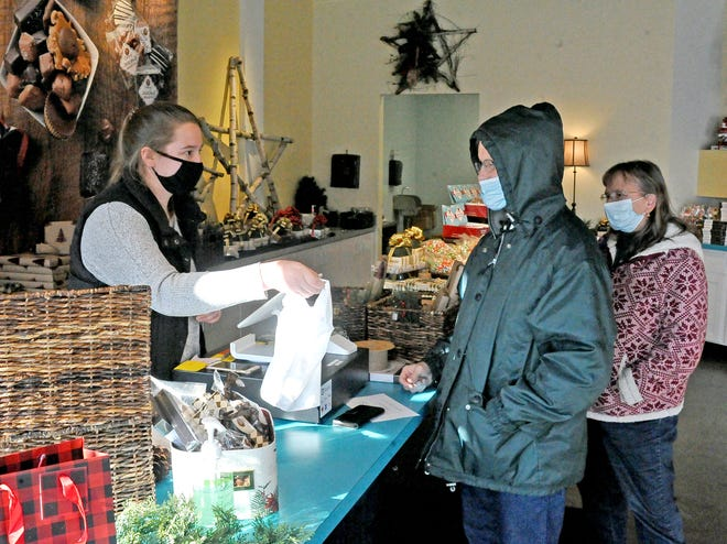 Chloe Boucher hands a purchase to Craig and Nancy Firestone, of Wooster, in the Wooster Holiday Store, which features Coblentz Chocolate, on West Liberty Street in downtown Wooster.