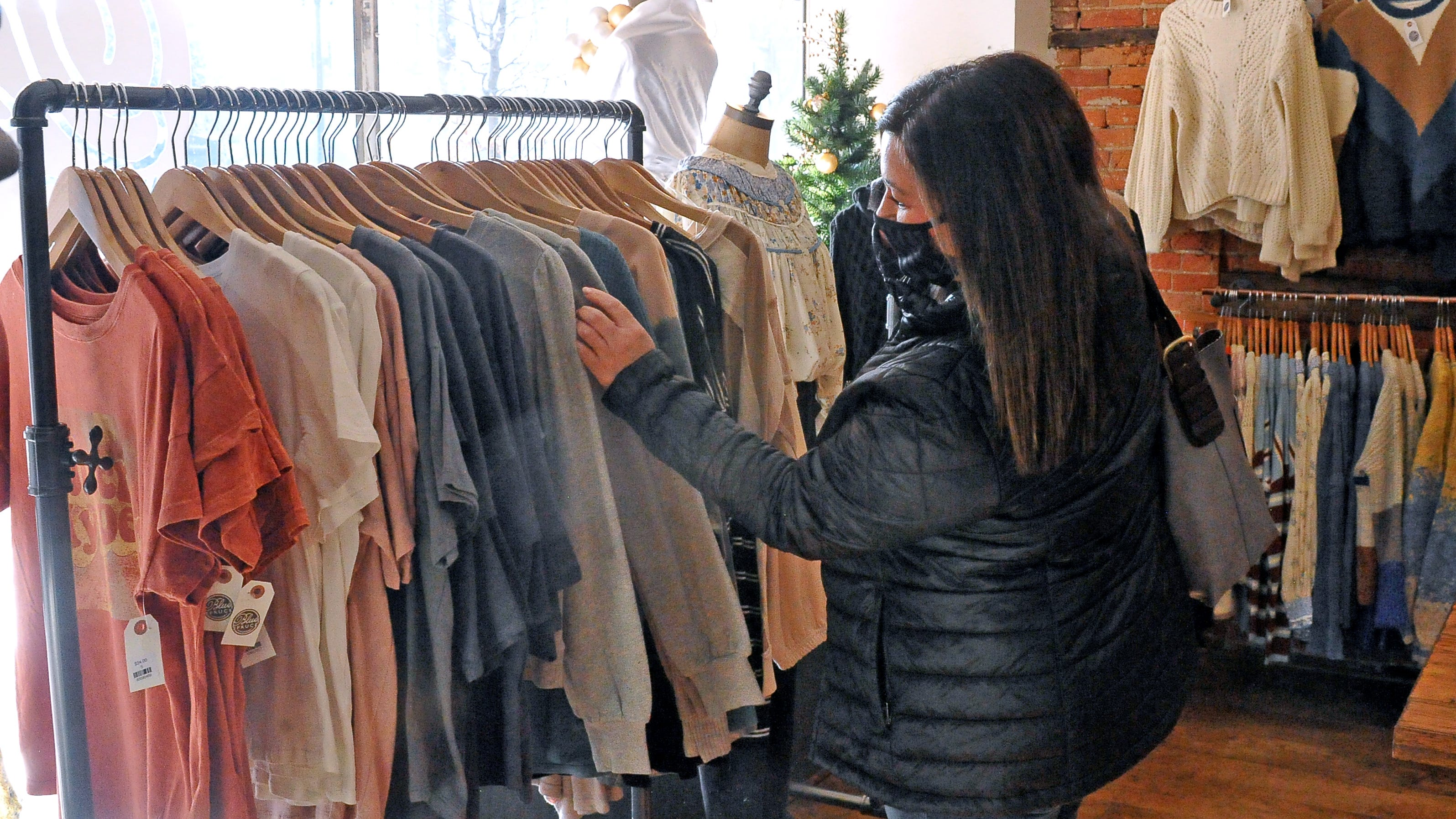 Susan Crilow, of Fredericksburg, checks out the sweater rack in the Blue Spruce on East Liberty Street in downtown Wooster.