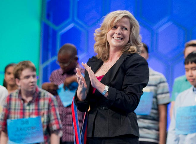 Paige Kimble, executive director of the Scripps National Spelling Bee, applauds during the 2014 bee. Scripps announced that Kimble is stepping down after 22 years in charge of the world's preeminent spelling competition.