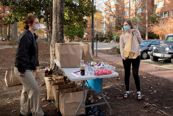 Jenny Deview, right, picks up meals from Jamie Sohn, a member of The Chapel Hill & Carrboro Mothers Club, which is providing free meals to UNC-Chapel Hill students staying on campus over their extended and isolated winter break during the COVID-19 pandemic.