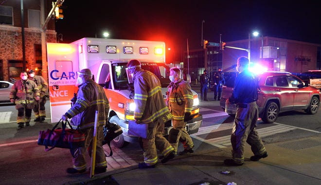Erie firefighters and EmergyCare personnel respond to an accident at 12th and State streets in Erie on Tuesday. A pedestrian was struck by a vehicle at the intersection around 9 p.m. The male victim was taken to the hospital with non-life-threatening injuries according to officials at the scene.