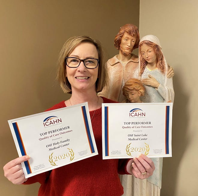 Jackie Kernan, president of OSF HealthCare Holy Family and Saint Luke Medical Center, holds excellence in quality-safety awards from the Illinois Critical Access Hospital Network.