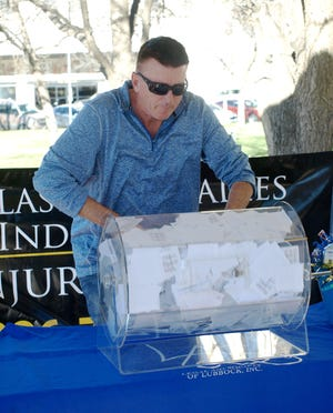 "Lubbock radio host Randy ""Mudflap"" Smith on Wednesday spins a raffle drum before drawing the winning ticket for a Winchester 26 gun safe at the Lubbock County Courthouse Gazebo as part of a fundraising event organized by the Legal Aid Society of Lubbock."