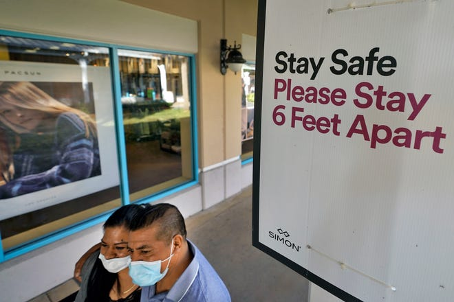 Shoppers wear protective face masks as they walk past a social distancing sign at the Ellenton Premium Outlet stores in Ellenton, Florida. Social distancing mandates have hindered the medical exams that are often required for life insurance applications. As a result, insurers increasingly use big data to decide who gets life insurance and at what price. [AP File Photo/Chris O'Meara]