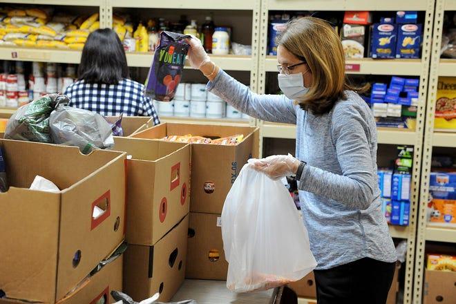 Detrás de escena en la despensa de alimentos Daily Bread en Milford, la voluntaria Maria Bella, de Milford, recolecta comestibles para los clientes.