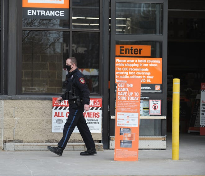 A Natick police officer in front of The Home Dept, following an armed robbery at Aldi at 321 Speen St. on Wednesday, Dec. 9, 2020.