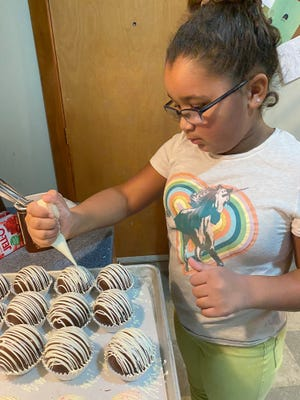 Alannah Calhoun, 9, of Newport puts the finishing touches on one of her hot chocolate bombs. The youngster has started her own business, Alannah's Bomb Shack.