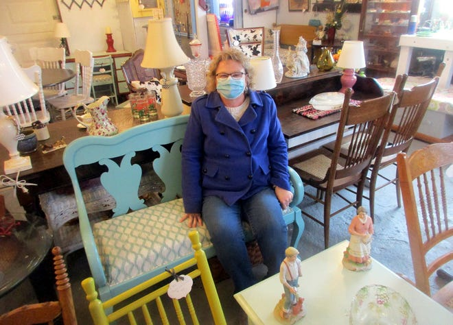 Andrea Kane poses Dec. 6 with some of the many refurbished and reloved treasures at the Valandrea's Venture shop she shares with sister Valerie Clark in Bouckville.