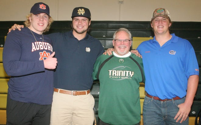 From left, Trinity Catholic's Garner Langlo, Caleb Johnson, Celtics head football coach John Brantley and Jake Slaughter are all smiles after Wednesday's signing ceremony in the Celtics gym.