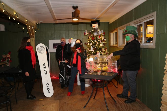 Bonnie Galinski, Festival of Trees (FOT) co-chair, announcing the winner of the White Claw themed raffle tree at Shooter's Pub on Dec. 3.  Also pictured are Lisa Lortie (FOT), Karen Drapaniotis of Exeter Area Charitable Foundation and Bill Arnold of Bayside Distributing LLC.