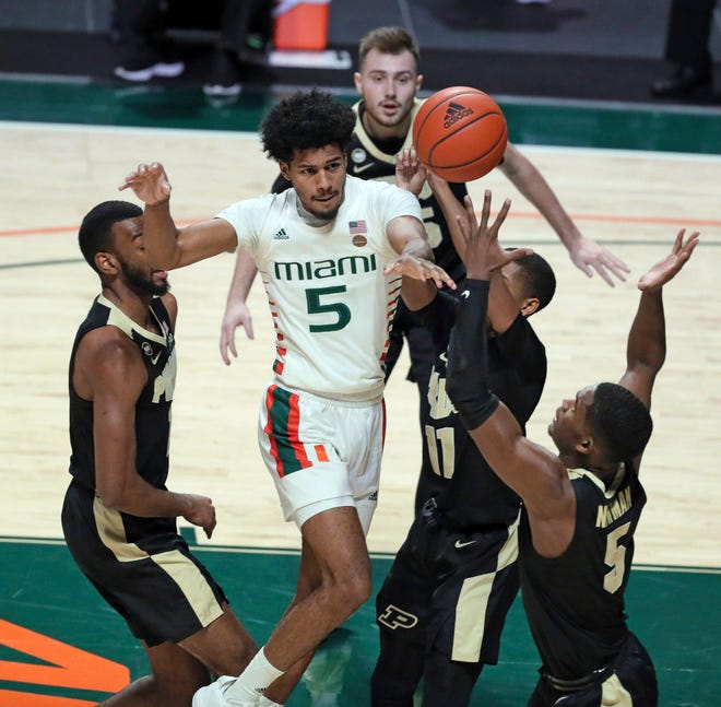 Miami guard Harlond Beverly (5) passes the ball around Purdue defenders during the first half of an NCAA college basketball game Tuesday, Dec. 8, 2020, in Coral Gables, Fla. (Al Diaz/Miami Herald via AP)