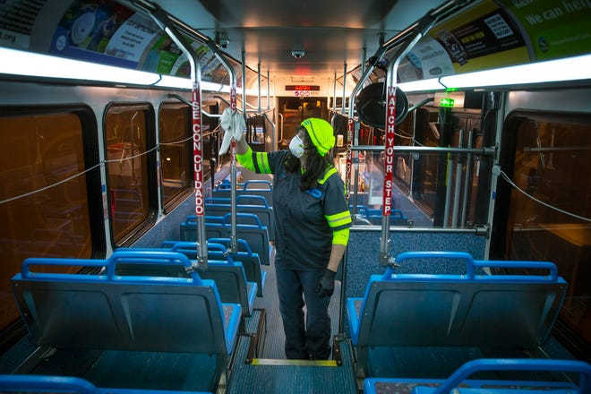 A Lane Transportation District worker wipes down the inside of a bus with disinfectant at the bus barn in Glenwood overnight as part of a plan to help prevent the spread of COVID-19 in the community.