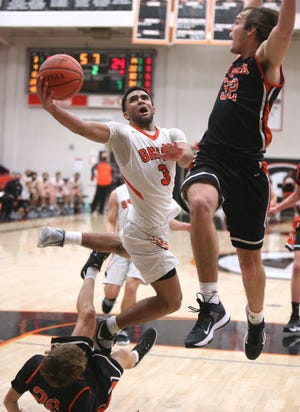 Trey Martin (3) of Green drives to the basket while being guarded by Brock Henne (20) of Hoover during their game at Green on Tuesday, Dec. 8, 2020.