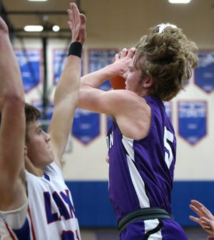 Ben Sullivan (5) of Jackson drives to the basket while being guarded by Caleb Collins (left) of Lake during their game at Lake on Tuesday, Dec. 8, 2020.