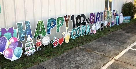 A sign celebrates Cora Moore for her 102nd birthday on Sunday.
