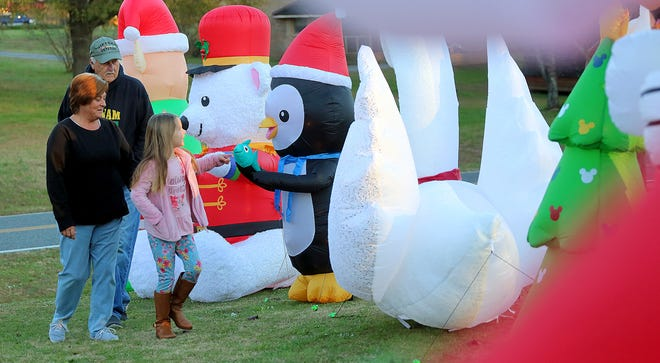 Steve and Christine Heflin take a walk through their Christmas display with neighbor Mia Blanton, 6, on Tuesday.