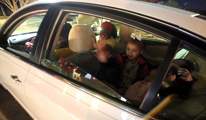 Adaya Degree, 2, waves to Santa from her car at Shelby City Park's drive-thru Carrousel Christmas on Tuesday.