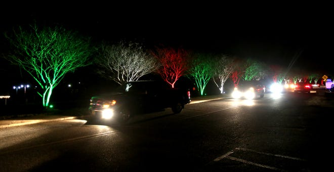 Cars make their way through Christmas lights to see Santa at Shelby City Park on Tuesday.