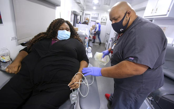 Jamel Autry prepares April McClain for blood donation at a community blood drive in Shelby on Wednesday. McClain plans to donate plasma if she has COVID-19 antibodies.